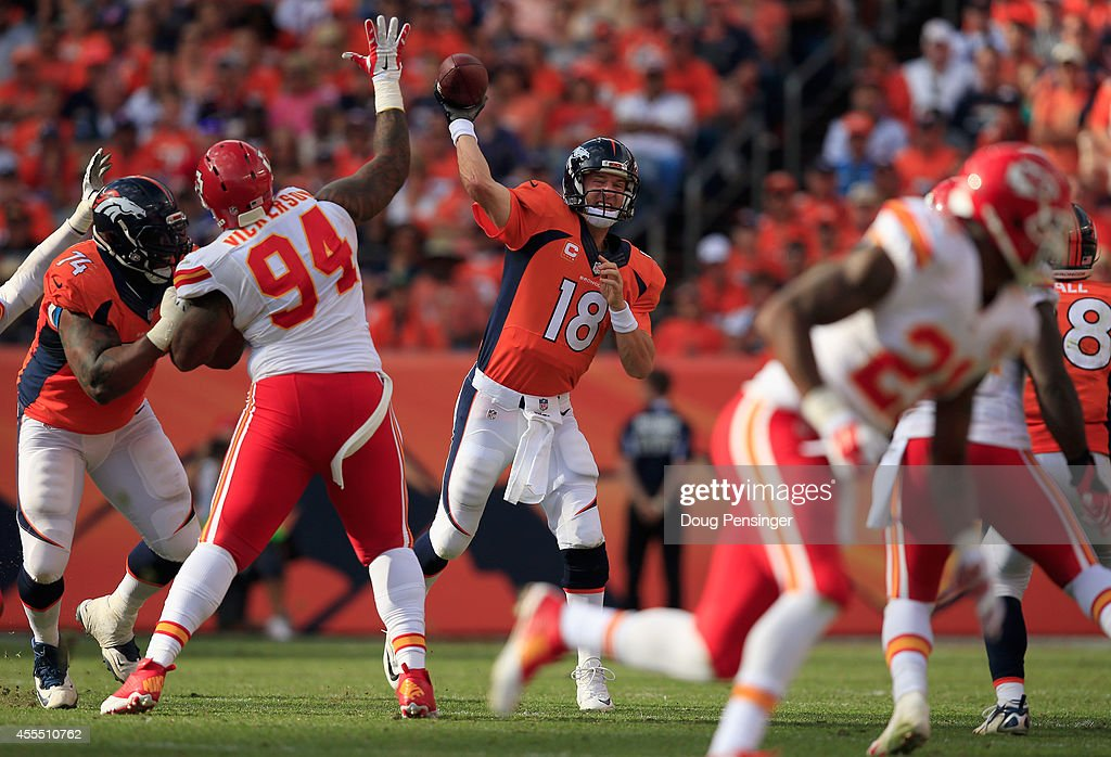 Quarterback Peyton Manning #18 of the Denver Broncos delivers a pass against the defense of Kevin Vickerson #94 of the Kansas City Chiefs at Sports Authority Field at Mile High on September 14, 2014 in Denver, Colorado. The Broncos defeated the Chiefs 24-17.