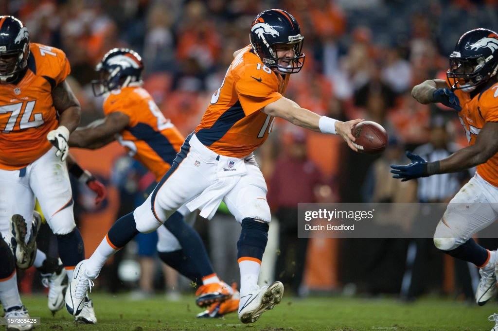 Quarterback <a gi-track='captionPersonalityLinkClicked' href=/galleries/search?phrase=Peyton+Manning&family=editorial&specificpeople=184524 ng-click='$event.stopPropagation()'>Peyton Manning</a> #18 of the Denver Broncos hands off the ball during a game against the Tampa Bay Buccaneers at Sports Authority Field Field at Mile High on December 2, 2012 in Denver, Colorado.