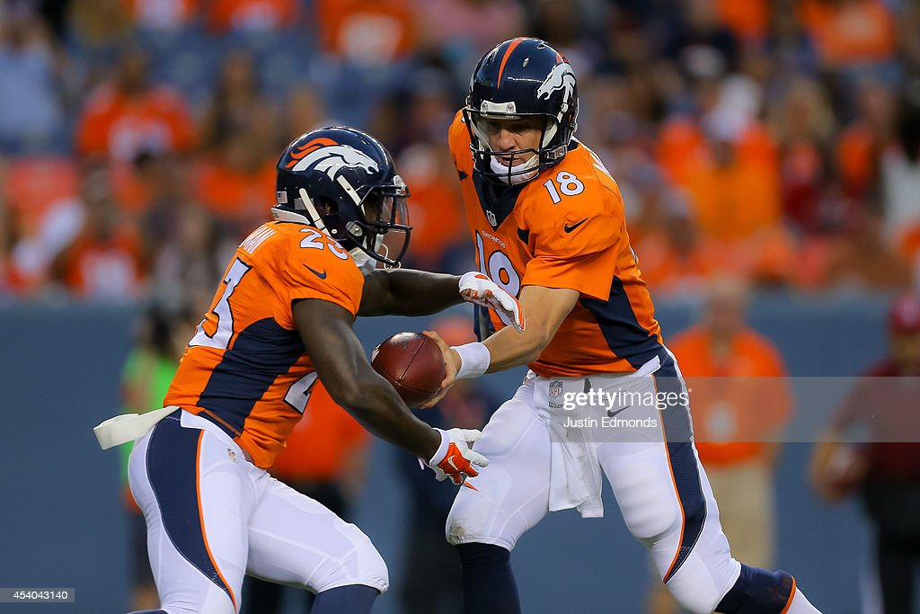 Quarterback <a gi-track='captionPersonalityLinkClicked' href=/galleries/search?phrase=Peyton+Manning&family=editorial&specificpeople=184524 ng-click='$event.stopPropagation()'>Peyton Manning</a> #18 of the Denver Broncos hands off to running back <a gi-track='captionPersonalityLinkClicked' href=/galleries/search?phrase=Ronnie+Hillman&family=editorial&specificpeople=7355403 ng-click='$event.stopPropagation()'>Ronnie Hillman</a> #23 during a preseason game at Sports Authority Field at Mile High on August 23, 2014 in Denver, Colorado.