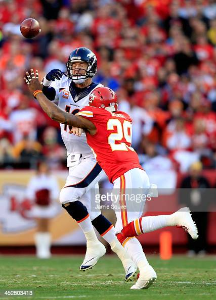 Quarterback Peyton Manning of the Denver Broncos is forced to throw the ball away as he is hurried by strong safety Eric Berry of the Kansas City...