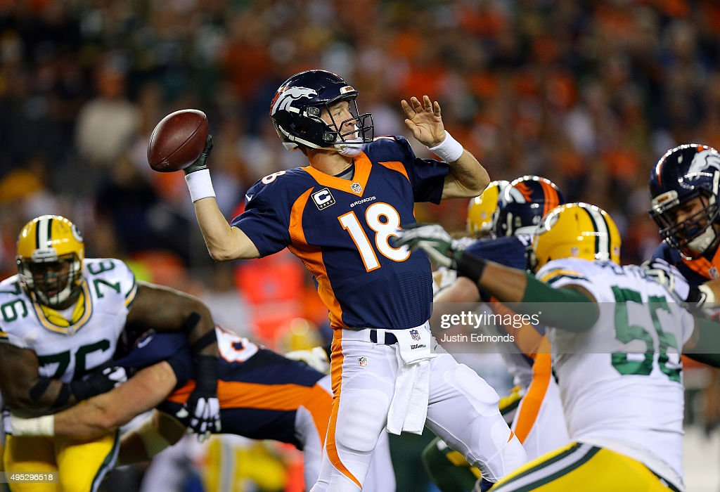 Quarterback Peyton Manning of the Denver Broncos looks to pass against Julius Peppers of the Green Bay Packers during the first quarter of the game...
