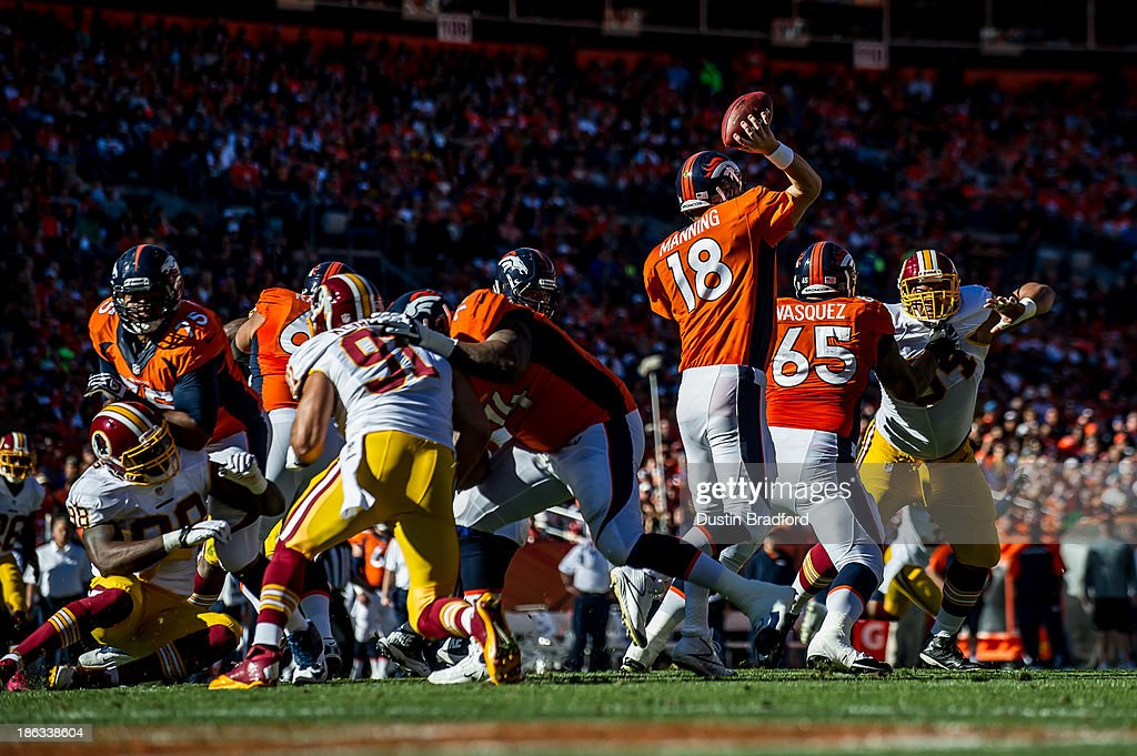 Quarterback Peyton Manning #18 of the Denver Broncos passes out of a collapsing pocket during a game against the Washington Redskins at Sports Authority Field Field at Mile High on October 27, 2013 in Denver, Colorado.