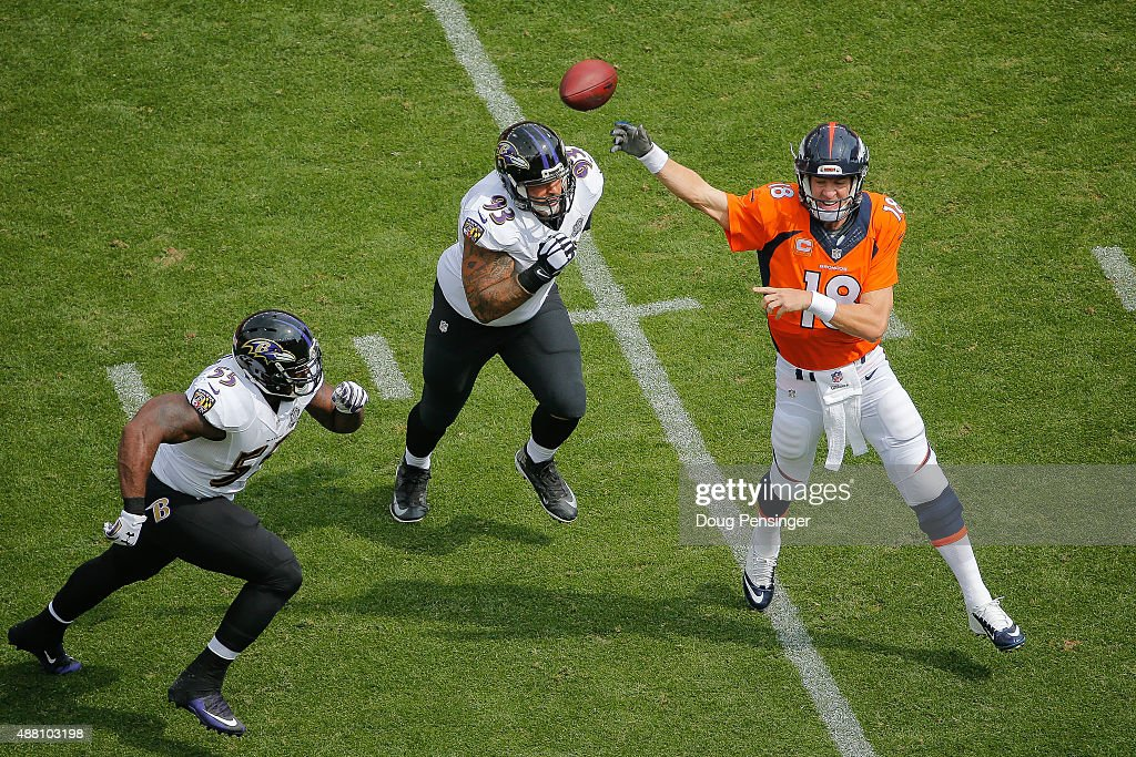 Quarterback Peyton Manning #18 of the Denver Broncos passes under pressure by outside linebacker Terrell Suggs #55 and defensive end Lawrence Guy #93 of the Baltimore Ravens in the first quarter of a game at Sports Authority Field at Mile High on September 13, 2015 in Denver, Colorado.