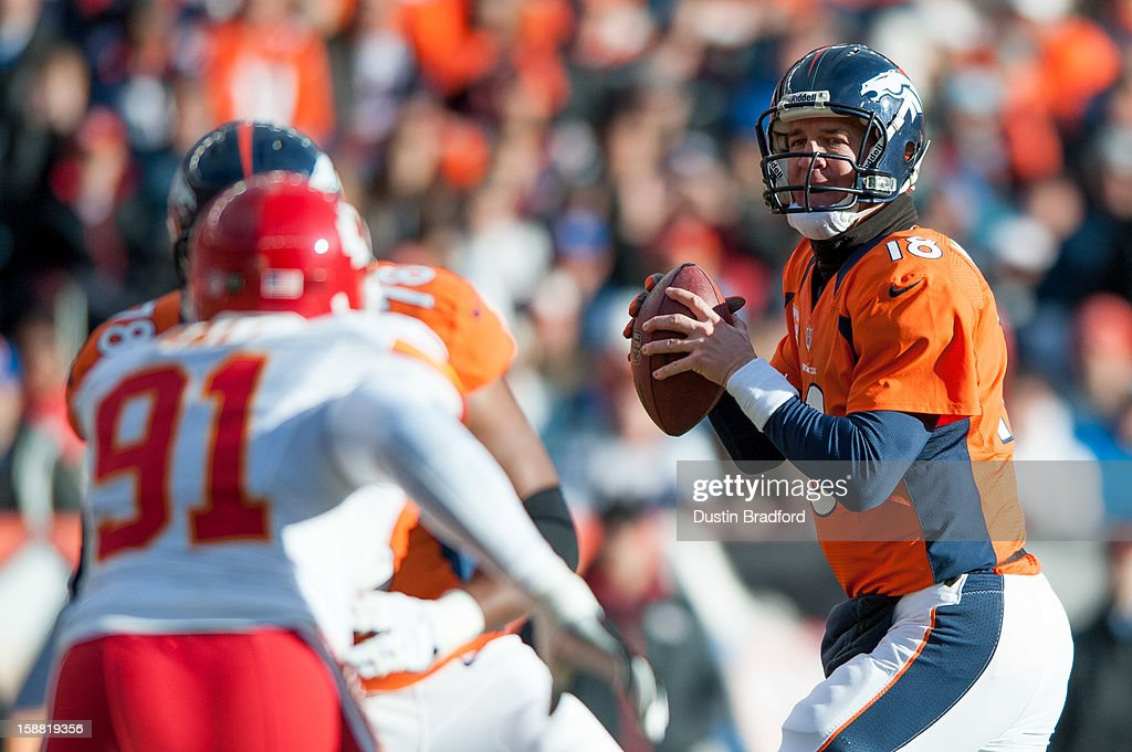 Quarterback Peyton Manning #18 of the Denver Broncos scans for an open receiver against the Kansas City Chiefs during a game at Sports Authority Field Field at Mile High on December 30, 2012 in Denver, Colorado.