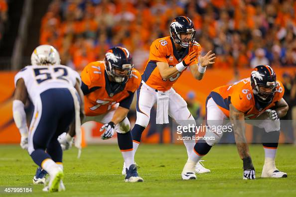 Quarterback Peyton Manning of the Denver Broncos signals at the line of scrimmage against the San Diego Chargers at Sports Authority Field at Mile...