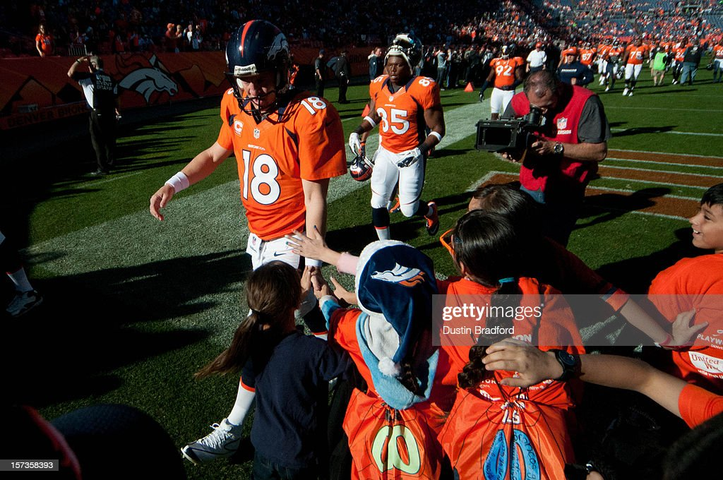 Quarterback Peyton Manning #18 of the Denver Broncos slaps five with kids on the sideline as he returns to the locker room before a game against the Tampa Bay Buccaneers at Sports Authority Field at Mile High on December 2, 2012 in Denver, Colorado.