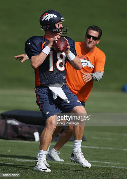 Quarterback Peyton Manning of the Denver Broncos takes part in a drill with quartbacks coach Greg Knapp during practice at the Paul D Bowlen Memorial...