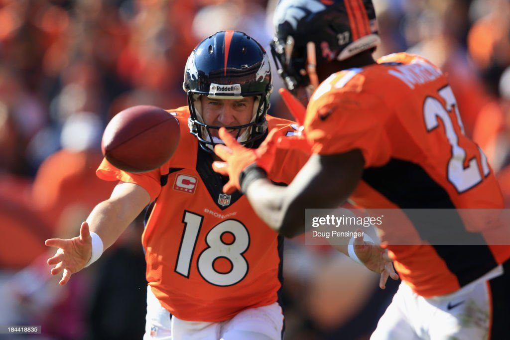 Quarterback <a gi-track='captionPersonalityLinkClicked' href=/galleries/search?phrase=Peyton+Manning&family=editorial&specificpeople=184524 ng-click='$event.stopPropagation()'>Peyton Manning</a> #18 of the Denver Broncos tosses the ball to running back <a gi-track='captionPersonalityLinkClicked' href=/galleries/search?phrase=Knowshon+Moreno&family=editorial&specificpeople=3986554 ng-click='$event.stopPropagation()'>Knowshon Moreno</a> #27 of the Denver Broncos against the Jacksonville Jaguars at Sports Authority Field at Mile High on October 13, 2013 in Denver, Colorado.