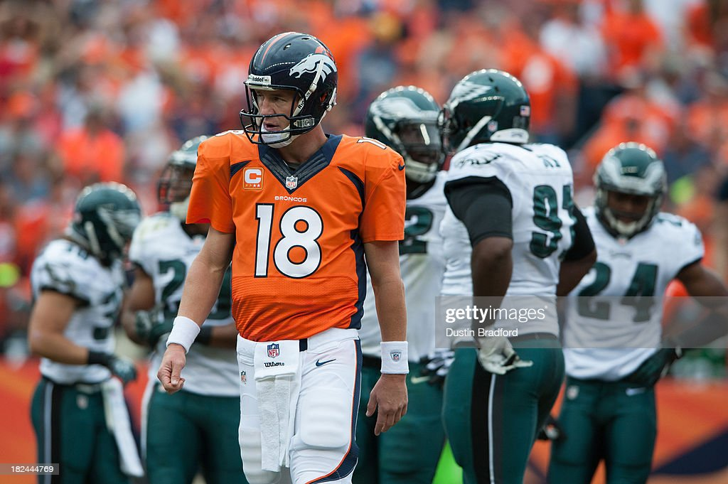 Quarterback Peyton Manning #18 of the Denver Broncos walks towards the bench during a break in the action during a game against the Philadelphia Eagles at Sports Authority Field Field at Mile High on September 29, 2013 in Denver, Colorado.
