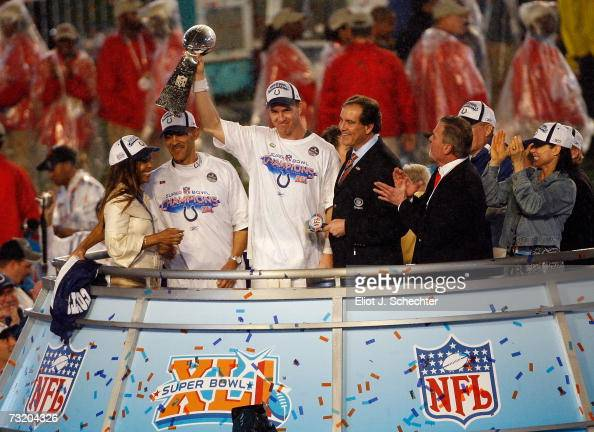 Quarterback Peyton Manning of the Indianapolis Colts celebrates with the Vince Lombardi Super Bowl trophy next to head coach Tony Dungy and is wife...