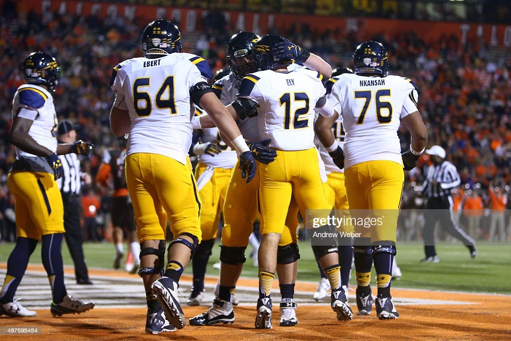 Quarterback Phillip Ely #12 of the Toledo Rockets celebrates with teammates after rushing for a touchdown during the third quarter against the Bowling Green Falcons at Doyt Perry Stadium on November 17, 2015 in Bowling Green, Ohio. Toledo defeated Bowling Green 44-28.