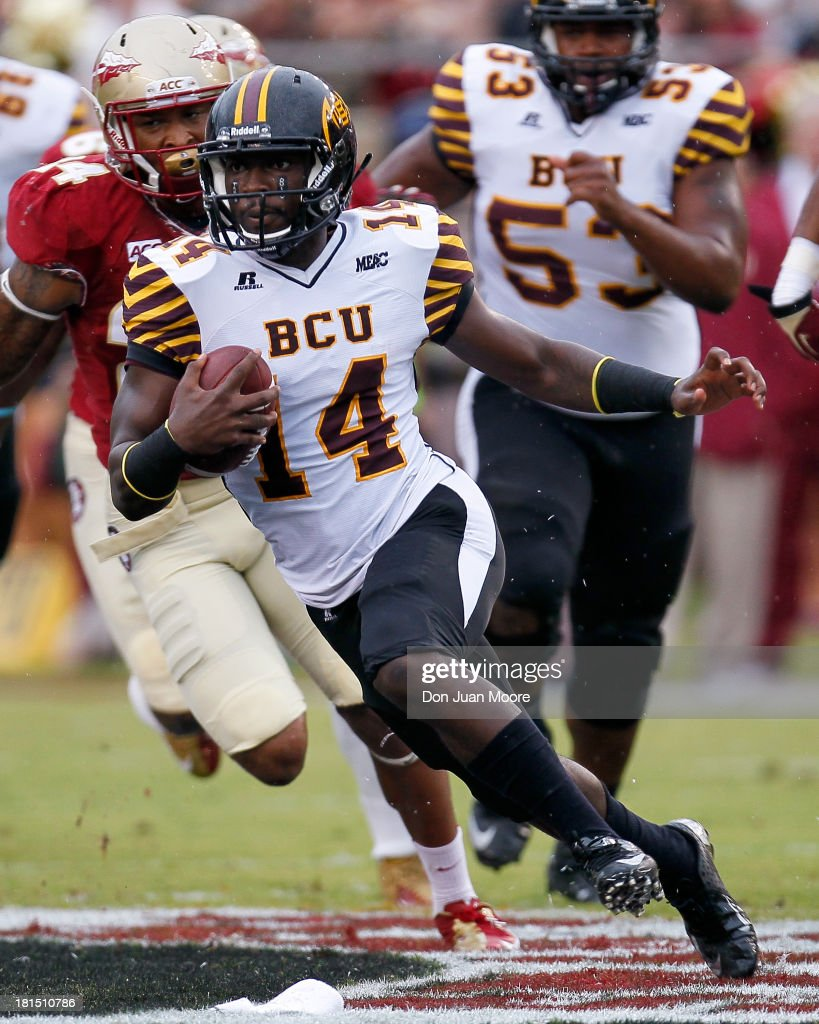 Quarterback Quentin Williams #14 of the Bethune-Cookman Wildcats runs for extra yards against the Florida State Seminoles at Doak Campbell Stadium on Bobby Bowden Field on September 21, 2013 in Tallahassee, Florida. The 8th ranked Florida State Seminoles defeated the Bethune-Cookman Wildcats 54-6.