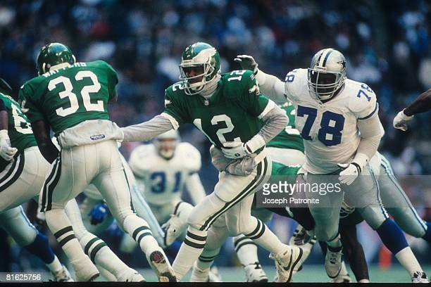 Quarterback Randall Cunningham of the Philadelphia Eagles hands off to running back Ricky Watters against the Dallas Cowboys at Texas Stadium in the...