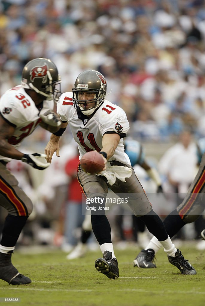 Quarterback Rob Johnson #11 of the Tampa Bay Buccaneers hands off the ball to Running Back Michael Pittman #32 against the Carolina Panthers during the NFL game at Ericsson Stadium on October 27, 2002 in Charlotte, North Carolina. The Buccaneers won 12-9.