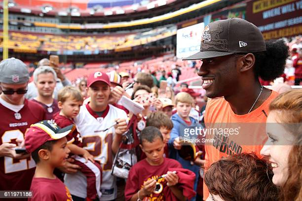 Quarterback Robert Griffin III of the Cleveland Browns poses for a photo with fans prior to a game against the Washington Redskins at FedExField on...