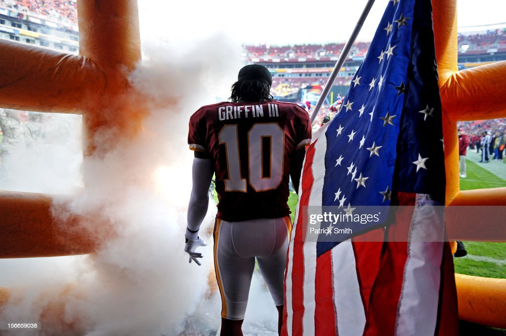 Quarterback <a gi-track='captionPersonalityLinkClicked' href=/galleries/search?phrase=Robert+Griffin&family=editorial&specificpeople=2495030 ng-click='$event.stopPropagation()'>Robert Griffin</a> III #10 of the Washington Redskins holds an American flag for Military Appreciation before being introduced against the Philadelphia Eagles at FedEx Field on November 18, 2012 in Landover, Maryland.