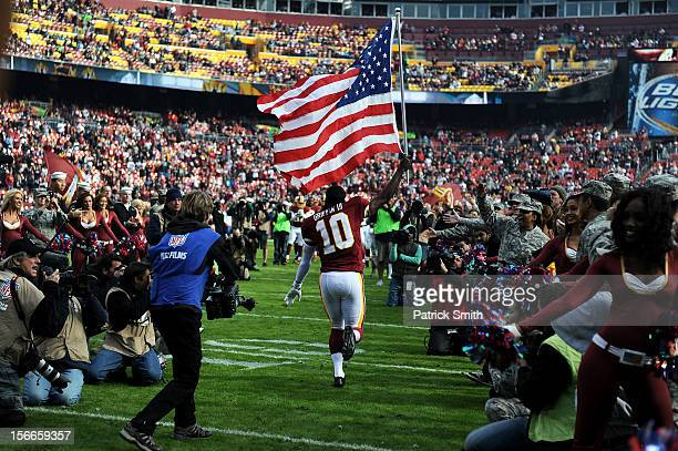 Quarterback Robert Griffin III of the Washington Redskins holds an American flag for Military Appreciation before being introduced against the...