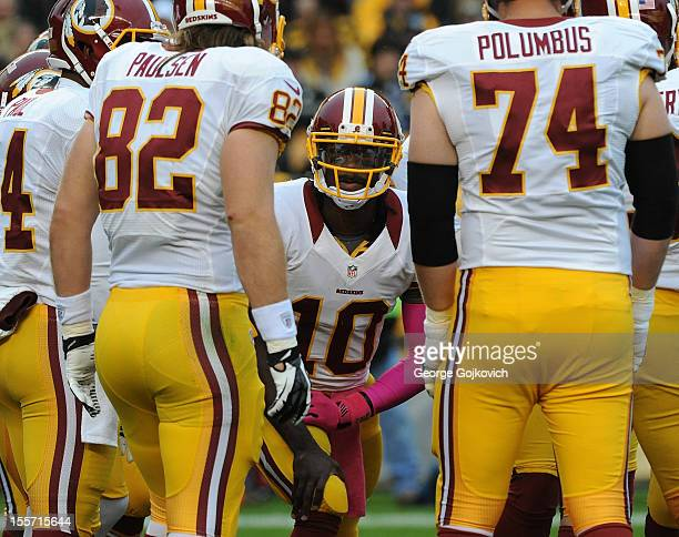 Quarterback Robert Griffin III of the Washington Redskins huddles with the offense including tight end Logan Paulsen and offensive tackle Tyler...