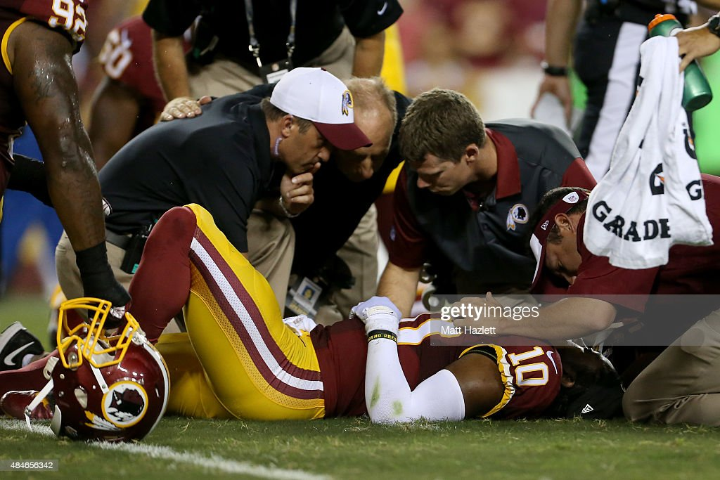 Quarterback Robert Griffin III #10 of the Washington Redskins is examined on the field during a preseason game against the Detroit Lines at FedExField on August 20, 2015 in Landover, Maryland.