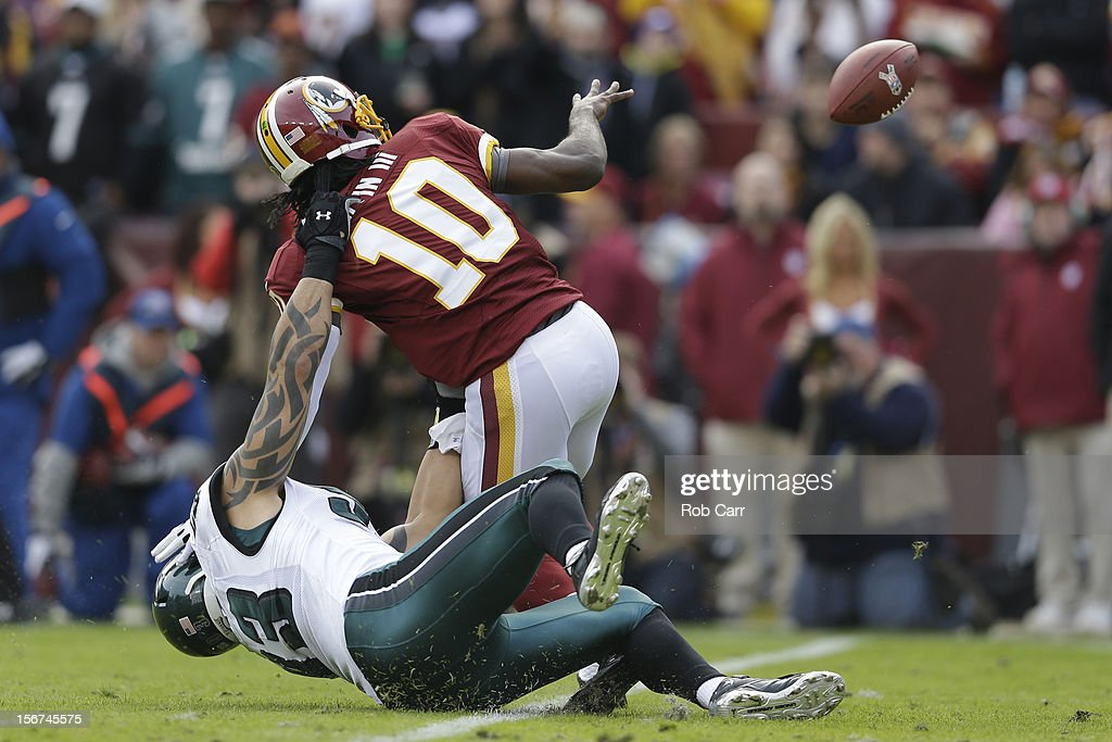 Quarterback Robert Griffin III #10 of the Washington Redskins pitches the ball while being tackled by defensive end Jason Babin #93 of the Philadelphia Eagles at FedEx Field on November 18, 2012 in Washington, DC.