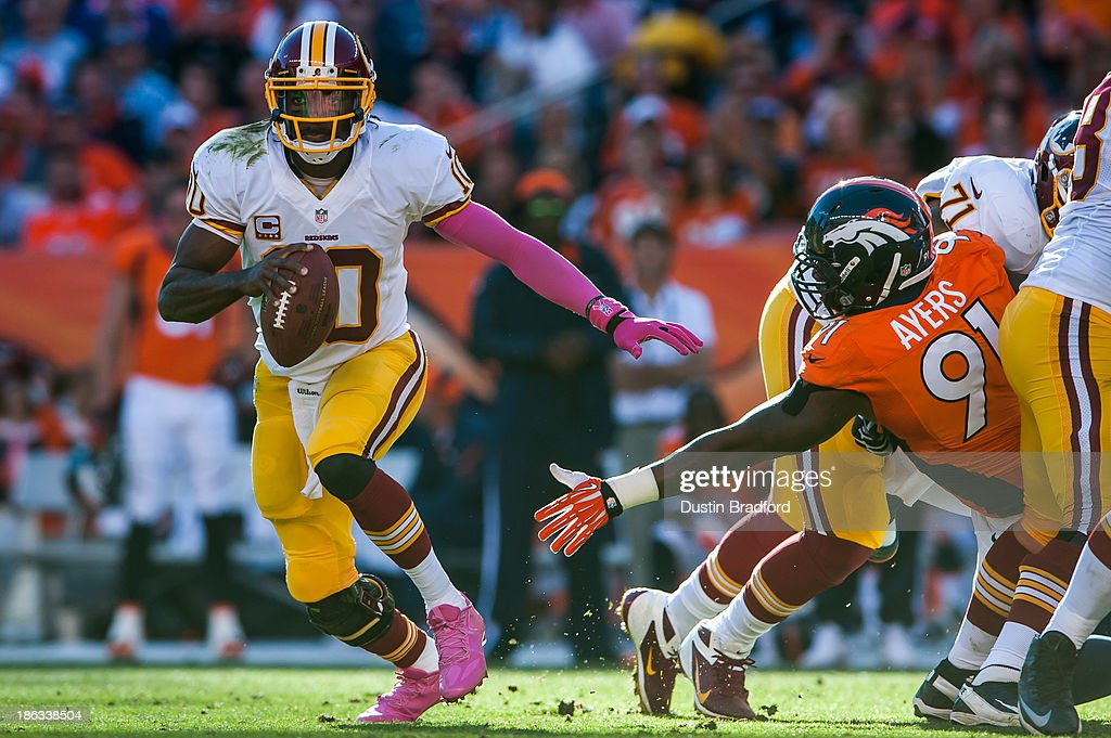 Quarterback <a gi-track='captionPersonalityLinkClicked' href=/galleries/search?phrase=Robert+Griffin&family=editorial&specificpeople=2495030 ng-click='$event.stopPropagation()'>Robert Griffin</a> III #10 of the Washington Redskins rolls out of the pocket during a game against the Denver Broncos at Sports Authority Field Field at Mile High on October 27, 2013 in Denver, Colorado.
