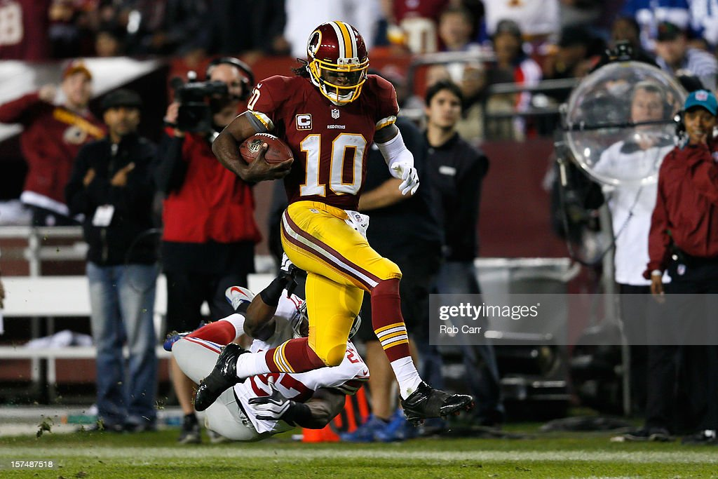 Quarterback <a gi-track='captionPersonalityLinkClicked' href=/galleries/search?phrase=Robert+Griffin&family=editorial&specificpeople=2495030 ng-click='$event.stopPropagation()'>Robert Griffin</a> III #10 of the Washington Redskins runs for a 46-yard gain as he is taken down by Stevie Brown #27 of the New York Giants in the second half at FedExField on December 3, 2012 in Landover, Maryland.