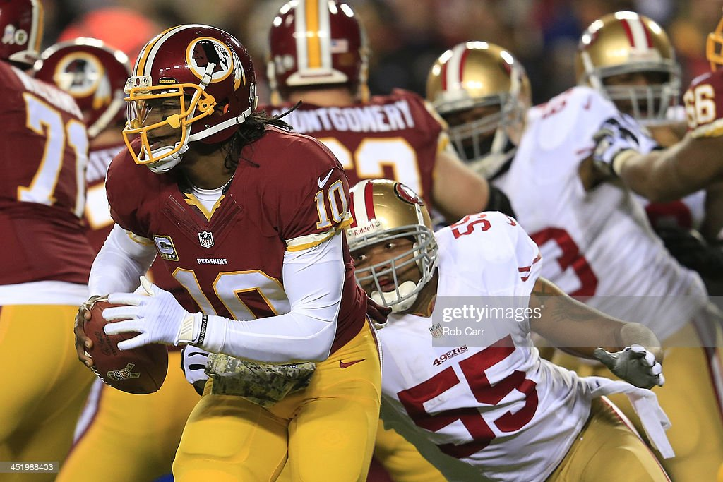 Quarterback <a gi-track='captionPersonalityLinkClicked' href=/galleries/search?phrase=Robert+Griffin&family=editorial&specificpeople=2495030 ng-click='$event.stopPropagation()'>Robert Griffin</a> III #10 of the Washington Redskins runs the ball as outside linebacker <a gi-track='captionPersonalityLinkClicked' href=/galleries/search?phrase=Ahmad+Brooks&family=editorial&specificpeople=2326499 ng-click='$event.stopPropagation()'>Ahmad Brooks</a> #55 of the San Francisco 49ers rushes in in the first quarter at FedExField on November 25, 2013 in Landover, Maryland.