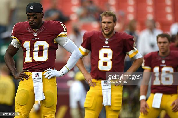 Quarterback Robert Griffin III quarterback Kirk Cousins and quarterback Colt McCoy of the Washington Redskins look on before playing the New England...