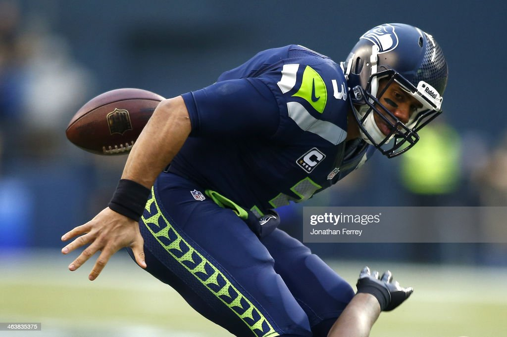 Quarterback <a gi-track='captionPersonalityLinkClicked' href=/galleries/search?phrase=Russell+Wilson+-+American+Football+Quarterback&family=editorial&specificpeople=2292912 ng-click='$event.stopPropagation()'>Russell Wilson</a> #3 of the Seattle Seahawks fumbles the ball in the first quarter after being tackled by outside linebacker Aldon Smith #99 of the San Francisco 49ers during the 2014 NFC Championship at CenturyLink Field on January 19, 2014 in Seattle, Washington.