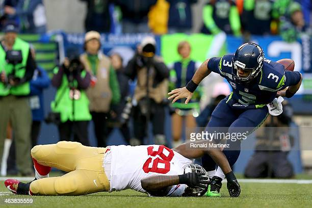 Quarterback Russell Wilson of the Seattle Seahawks fumbles the ball in the first quarter as he is tackled by outside linebacker Aldon Smith of the...