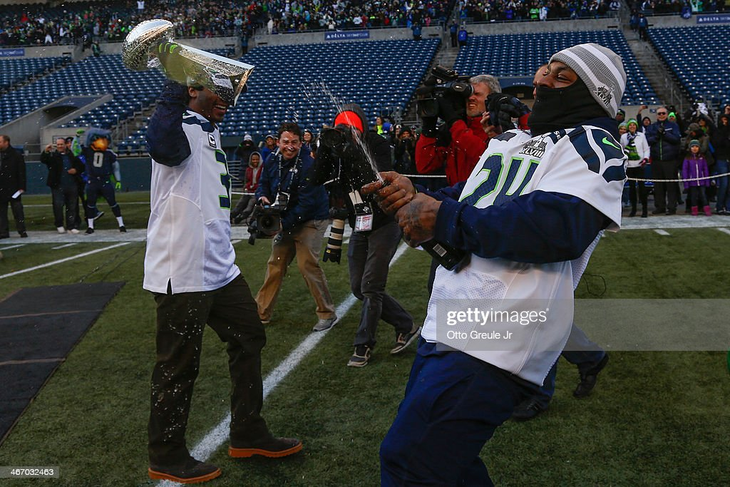 Quarterback <a gi-track='captionPersonalityLinkClicked' href=/galleries/search?phrase=Russell+Wilson+-+American+Football+Quarterback&family=editorial&specificpeople=2292912 ng-click='$event.stopPropagation()'>Russell Wilson</a> (L) of the Seattle Seahawks holds the Lombardi Trophy as Running back <a gi-track='captionPersonalityLinkClicked' href=/galleries/search?phrase=Marshawn+Lynch&family=editorial&specificpeople=2159904 ng-click='$event.stopPropagation()'>Marshawn Lynch</a> #24 uncorks a bottle of champagne during ceremonies following the Seahawks' Super Bowl XLVIII Victory Parade at CenturyLink Field on February 5, 2014 in Seattle, Washington.