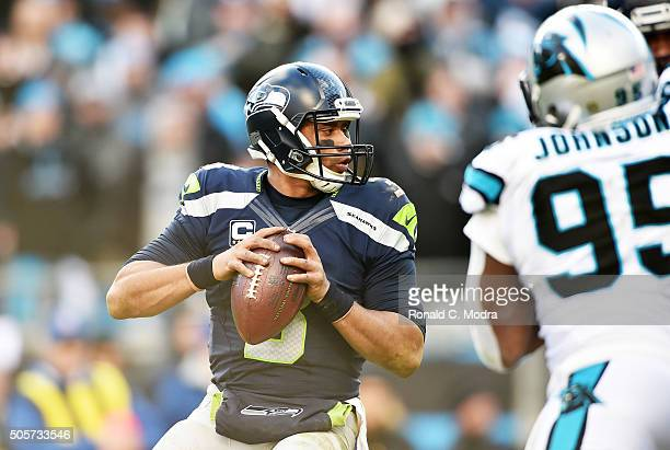 Quarterback Russell Wilson of the Seattle Seahawks looks for a receiver during the NFC Divisional Playoff Game against the Carolina Panthers at Bank...