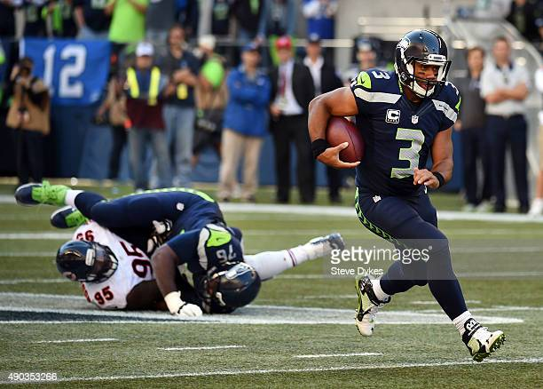 Quarterback Russell Wilson of the Seattle Seahawks runs with the ball as tackle Russell Okung of the Seattle Seahawks blocks defensive line man Ego...