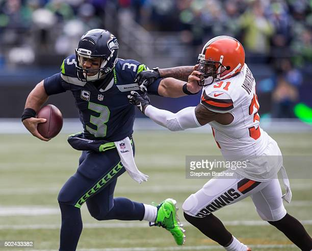 ... Game Jersey Quarterback Russell Wilson of the Seattle Seahawks runs  with the ball as defensive back Donte Whitner Nike Cleveland Browns 31 ... 98af293d9