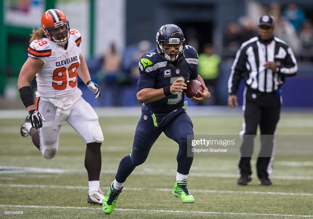 Quarterback <a gi-track='captionPersonalityLinkClicked' href=/galleries/search?phrase=Russell+Wilson+-+American+Football+Quarterback&family=editorial&specificpeople=2292912 ng-click='$event.stopPropagation()'>Russell Wilson</a> #3 of the Seattle Seahawks runs with the ball as he is chased by defensive lineman <a gi-track='captionPersonalityLinkClicked' href=/galleries/search?phrase=Paul+Kruger+-+American+Football+Player&family=editorial&specificpeople=10177986 ng-click='$event.stopPropagation()'>Paul Kruger</a> #99 of the Cleveland Browns during the first half a football game at CenturyLink Field on December 20, 2015 in Seattle, Washington.