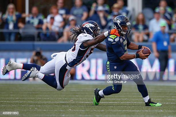 Quarterback Russell Wilson of the Seattle Seahawks rushes against linebacker Nate Irving of the Denver Broncos at CenturyLink Field on September 21...