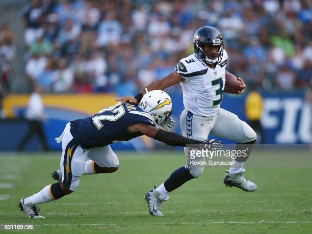 Quarterback Russell Wilson of the Seattle Seahawks scrambles out of the pocket as he is chased by cornerback Trevor Williams of the Los Angeles...