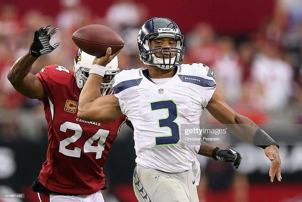 Quarterback <a gi-track='captionPersonalityLinkClicked' href=/galleries/search?phrase=Russell+Wilson+-+American+Football+Quarterback&family=editorial&specificpeople=2292912 ng-click='$event.stopPropagation()'>Russell Wilson</a> #3 of the Seattle Seahawks throws a pass under pressure from strong safety <a gi-track='captionPersonalityLinkClicked' href=/galleries/search?phrase=Adrian+Wilson+-+American+Football+Player&family=editorial&specificpeople=773272 ng-click='$event.stopPropagation()'>Adrian Wilson</a> #24 of the Arizona Cardinals during the season opener at the University of Phoenix Stadium on September 9, 2012 in Glendale, Arizona. The Cardinals defeated the Seahawks 20-16.