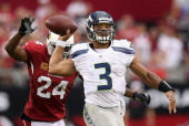 Quarterback Russell Wilson of the Seattle Seahawks throws a pass under pressure from strong safety Adrian Wilson of the Arizona Cardinals during the...