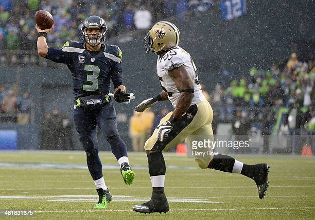 Quarterback Russell Wilson of the Seattle Seahawks throws the ball against defensive end Keyunta Dawson of the New Orleans Saints in the second...