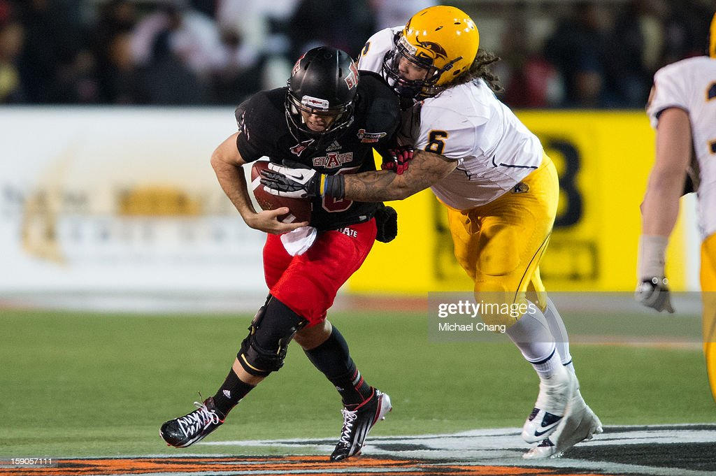Quarterback Ryan Aplin #16 of the Arkansas State Red Wolves attempts to elude a tackle by defensive lineman Dana Brown Jr. #6 of the Kent State Golden Flashes on January 6, 2013 at Ladd-Peebles Stadium in Mobile, Alabama. Arkansas State defeated Kent State 17-13.