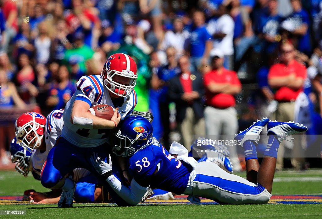 Quarterback Ryan Higgins #14 of the Louisiana Tech Bulldogs is tackled by linebacker Courtney Arnick #58 of the Kansas Jayhawks after scrambling during the game at Memorial Stadium on September 21, 2013 in Lawrence, Kansas.