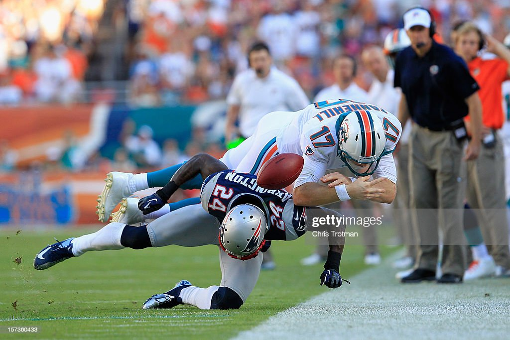 Quarterback Ryan Tannehill #17 of the Miami Dolphins is hit by cornerback Kyle Arrington #24 of the New England Patriots as head coach Joe Philbin of the Miami Dolphins looks on at Sun Life Stadium on December 2, 2012 in Miami Gardens, Florida.