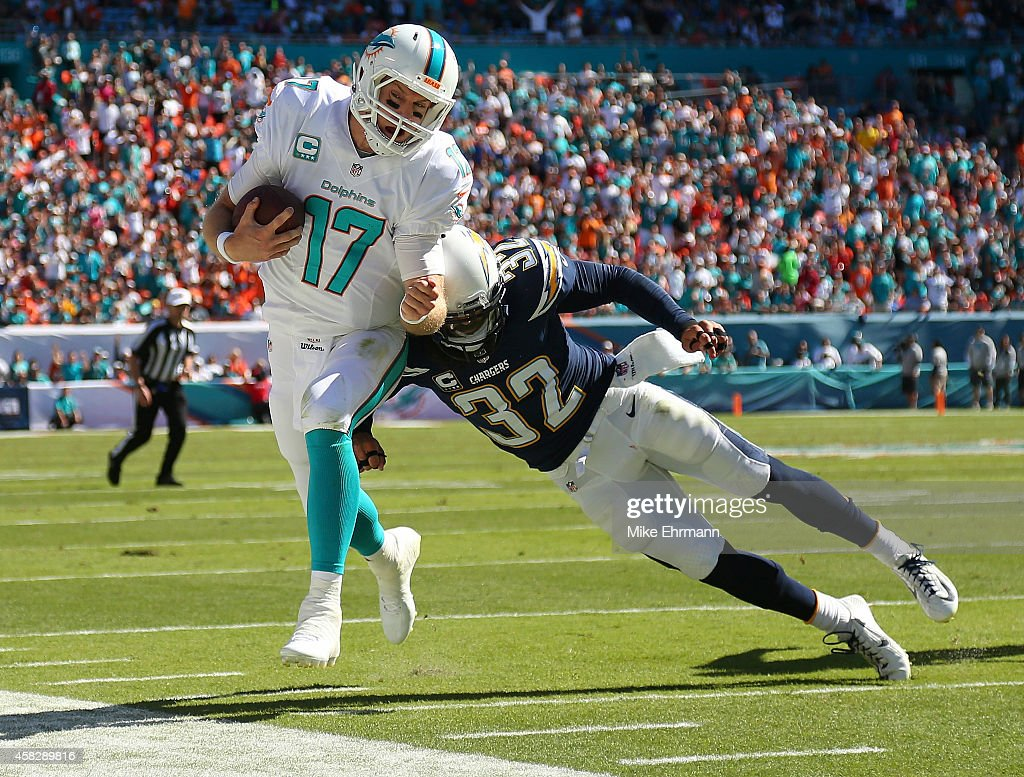 Quarterback <a gi-track='captionPersonalityLinkClicked' href=/galleries/search?phrase=Ryan+Tannehill&family=editorial&specificpeople=5573174 ng-click='$event.stopPropagation()'>Ryan Tannehill</a> #17 of the Miami Dolphins is knocked out of bounds by free safety <a gi-track='captionPersonalityLinkClicked' href=/galleries/search?phrase=Eric+Weddle&family=editorial&specificpeople=2630547 ng-click='$event.stopPropagation()'>Eric Weddle</a> #32 of the San Diego Chargers in the second quarter during a game at Sun Life Stadium on November 2, 2014 in Miami Gardens, Florida.