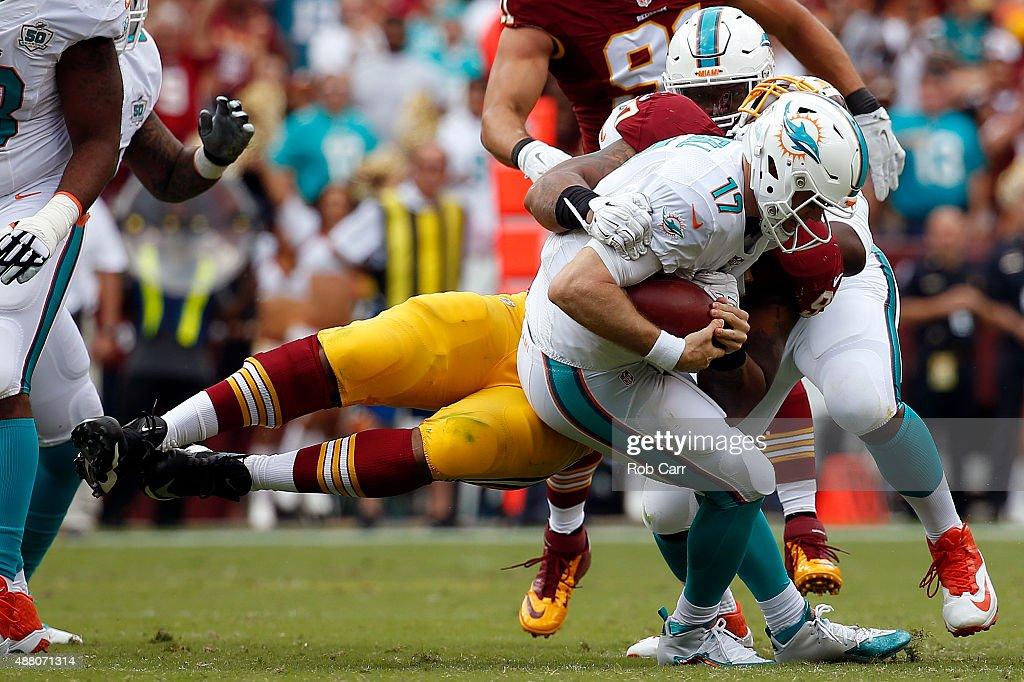 Quarterback Ryan Tannehill of the Miami Dolphins is sacked by defensive end Jason Hatcher of the Washington Redskins in the first half of a game at...