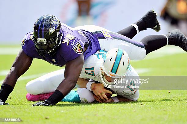 Quarterback Ryan Tannehill of the Miami Dolphins is tackled by linebacker Elvis Dumervil of the Baltimore Ravens during an NFL game at Sun Life...
