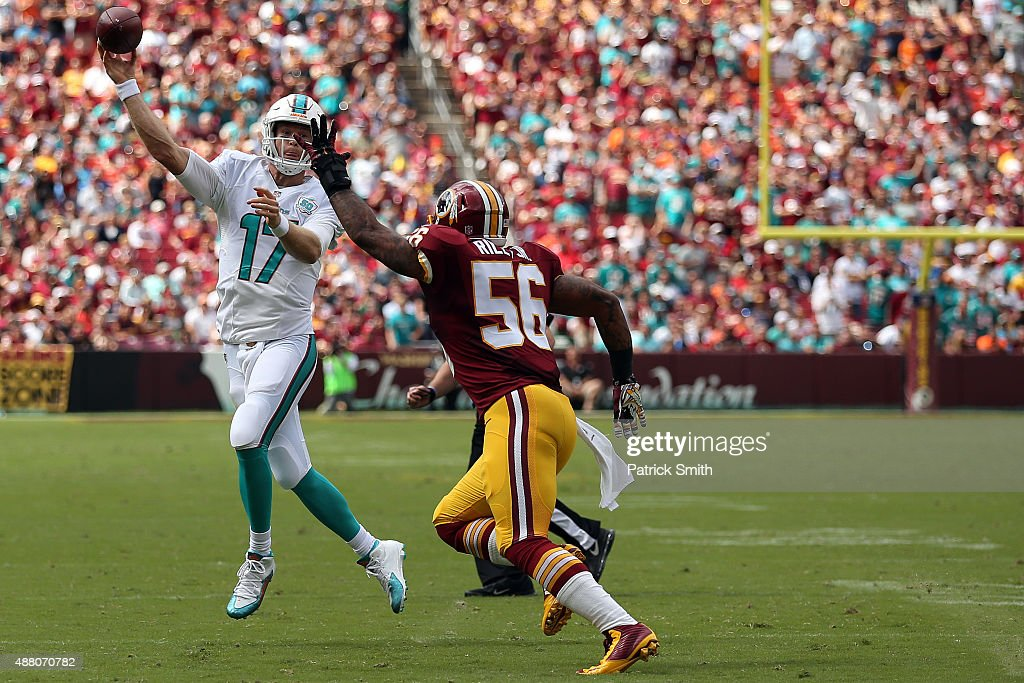 Quarterback Ryan Tannehill of the Miami Dolphins throws the ball while inside linebacker Perry Riley of the Washington Redskins defends in the first...