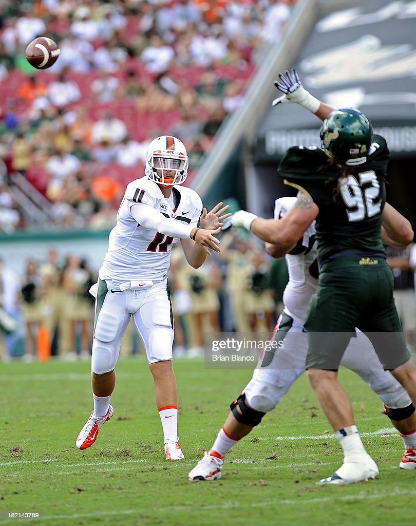 Quarterback Ryan Williams #11 of the Miami Hurricanes gets some help stopping defensive tackle Luke Sager #92 of the South Florida Bulls from teammate, offensive linesman Brandon Linder #65 as he throws to an open receiver during the second quarter against the South Florida Bulls on September 28, 2013 at Raymond James Stadium in Tampa, Florida.