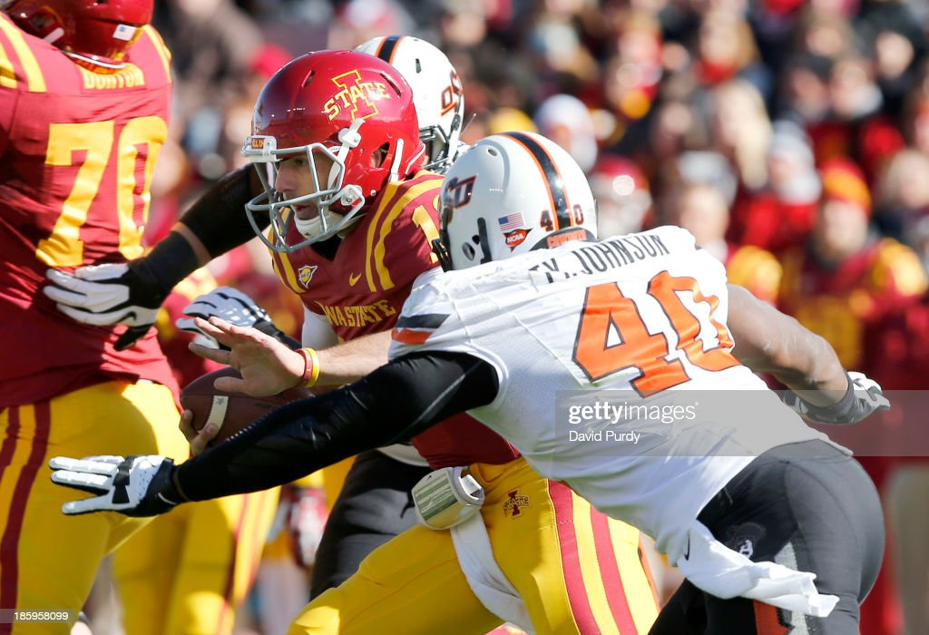 Quarterback Sam B. Richardson #12 of the Iowa State Cyclones is tackled by defensive end Tyler Johnson #40 of the Oklahoma State Cowboys while scrambling for yards in the first half of play at Jack Trice Stadium on October 26, 2013 in Ames, Iowa. The Oklahoma State Cowboys defeated the Iowa State Cyclones 58-27.