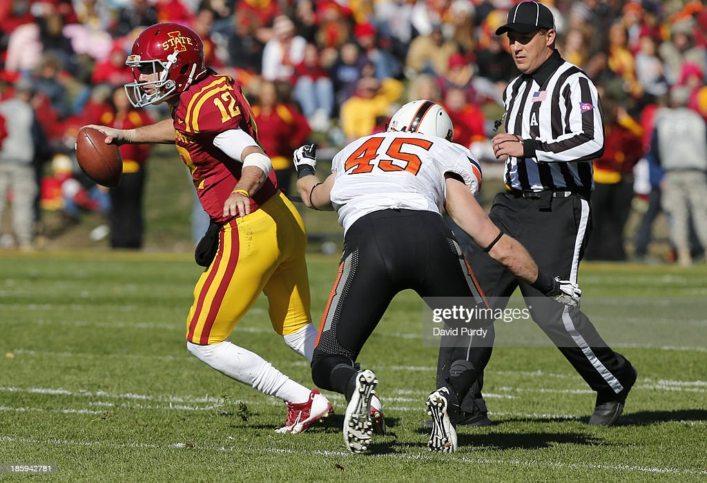 Quarterback Sam B. Richardson #12 of the Iowa State Cyclones scrambles under pressure from linebacker Caleb Lavey #45 of the Oklahoma State Cowboys in the first half of play at Jack Trice Stadium on October 26, 2013 in Ames, Iowa.